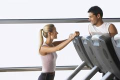 Trainer Conversing With Man On Treadmill - stock photo