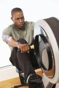 Man Working Out On Rowing Machine Stock Photos