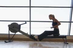 Women Using Rowing Machine In Health Club Stock Photos