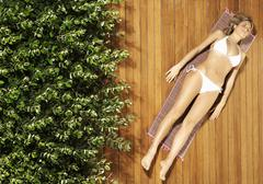 Stock Photo of Young Woman In Bikini Sunbathing On Patio