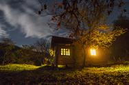 Stock Photo of cottage in a mystical night scene with stars on the sky