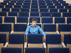 Businessman Sitting Alone On In Auditorium - stock photo