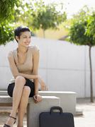 Stock Photo of Businesswoman Sitting On Bench In Plaza