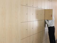 Businessman Putting Head In Small Locker - stock photo