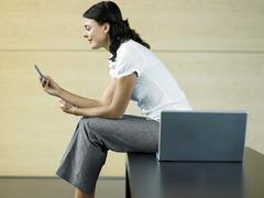 Businesswoman Reading Text Message In Lobby Stock Photos