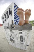 Germany, Lower Saxony, East Frisia, Langeoog, feet on an armrest of a roofed Stock Photos