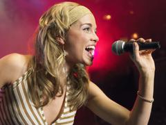 Closeup Of Young Woman Singing Into Microphone Stock Photos