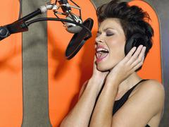 Stock Photo of Young Woman Singing In Studio