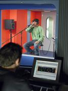 Young Man Singing With Studio Technician In Foreground Stock Photos