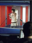 Young Woman Singing With Studio Technician In Foreground Stock Photos