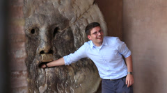 A couple try out the Mouth of Truth in Rome Stock Footage