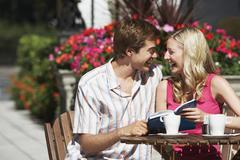 Happy Couple With Guidebook Sitting At Outdoor Cafe Stock Photos