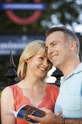 Loving Couple With Guidebook Outdoors - stock photo