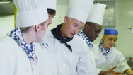 Stock Video Footage of Team of professional chefs preparing food in a commercial kitchen