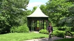 Woman walking by gazebo in park Stock Footage