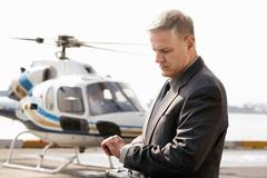 Businessman Checking Time At The Helicopter Pad - stock photo