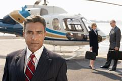 Businessman With Colleagues By Helicopter In Background Stock Photos