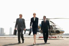 Businesspeople Arriving From Helicopter - stock photo
