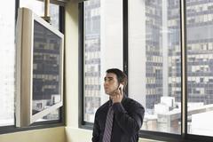 Liikemies katsot plasmatelevisio samalla viestintä matkapuhelimeen Kuvituskuvat