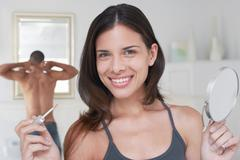 Happy Woman Holding Applicator And Mirror - stock photo