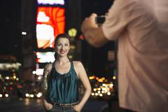 Man Photographing Woman In Times Square At Night Stock Photos