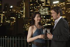 Couple With champagne Flutes Against Cityscape At Night Stock Photos