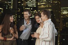 Couples Drinking Against City Skyline At Night Stock Photos