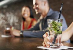 Cocktail Glass With Blurred Couple Behind - stock photo