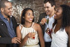 Couples With Drinks At Bar - stock photo