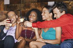 Multiethnic Friends Toasting Drinks In Bar - stock photo