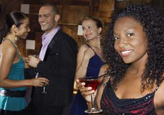 Woman Holding Drink With People At Bar - stock photo
