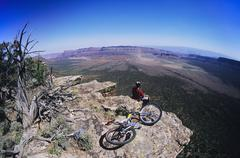 Mountain Biker On Rock Looking At View - stock photo