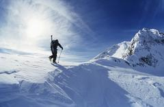 Skier Hiking To Mountain Summit - stock photo