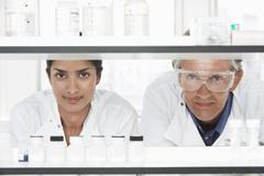 Scientists Looking Through Shelves Stock Photos