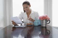 Stock Photo of Businesswoman Having Sandwich While Reading Document At Home