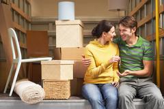 Couple Holding Key While Sitting Back Of Moving Van - stock photo