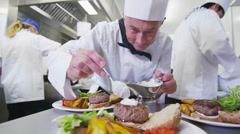 Delicious meal being given the finishing touches by chef in a commercial kitchen - stock footage