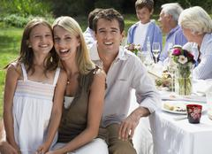 Happy Family Dining At Table In Garden - stock photo