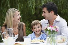 Happy Parents With Son Sitting At Dining Table In Garden Stock Photos