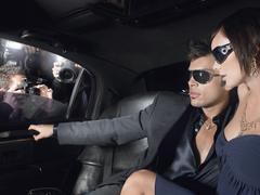 Couple In Limousine With Paparazzi By Window - stock photo