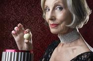 Stock Photo of Wealthy Senior Woman With Candy Box