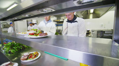 Mixed ethnicity team of professional chefs preparing food ready for service - stock footage