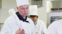Head chef in commercial kitchen overseeing staff and offering advice Stock Footage