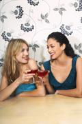 Women Toasting Drinks Against Floral Print Wall - stock photo