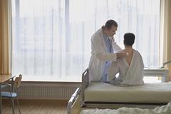 Doctor Examining Patient In Hospital Room Stock Photos
