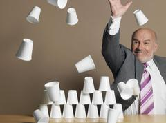 Businessman Knocking Down Pyramid Of Cups - stock photo