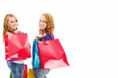 two happy women with shopping bags turning around - stock photo