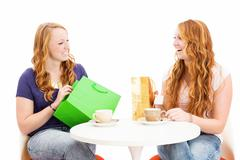two happy redhead women sitting at a coffee table with shopping bags - stock photo