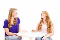 Happy women sitting at a coffee table Stock Photos