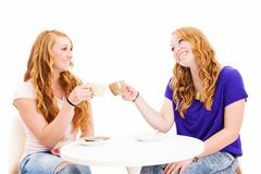 two happy redhead women clink glasses with coffee cups - stock photo